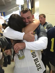 Michael Hirsch hugs younger sister Ellen after Saturday's game, in which he caught a pass for 15 yards.