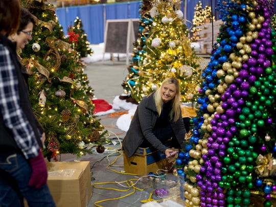 Ellen Dunkelberger, of Lexington, talks with others as she decorates a tree with hundreds of ornaments in preparation for the Festival of Trees Wednesday, December 2, 2015 at McMorran Arena in Port Huron.