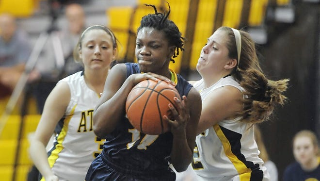 Webster Thomas' Candaisy Crawford, center, rips a rebound away from Greece Athena's Carina Pringle, right, during a regular season game played at Greece Athena last season.