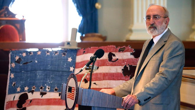 In a Dec. 10, 2013 file photo, Mississippi Department of Archives and History executive director Hank Holmes speaks about the digital replica of the rare 20-star U.S. flag that marked Mississippi's statehood in 1817, in Jackson, Miss.  Holmes is retiring next year after what will be 42 years at the Mississippi Department of Archives and History, nine as executive director. Holmes said Katrina was the biggest recovery effort his agency has undertaken.