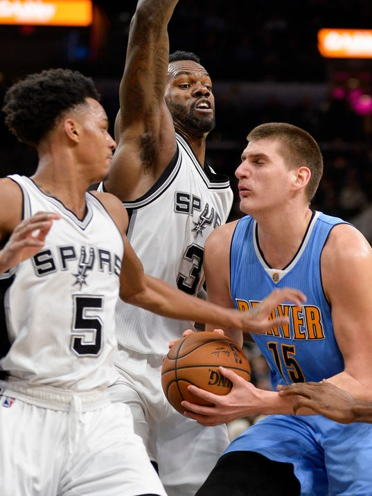 Denver Nuggets center Nikola Jokic (15), of Serbia, attempts to drive the lane against San Antonio Spurs' Dejounte Murray (5) and Dewayne Dedmon during the first half of an NBA basketball game, Thursday, Jan. 19, 2017, in San Antonio. (AP Photo/Darren Abate)