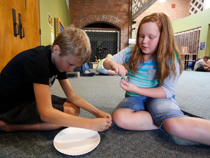 Cale Bussen, 10, and Megan Storther, 10, take part in a hands on activity at the Discover Center during a parent meeting for the Academy of Exploration on Tuesday, July 29, 2014. Springfield Public SchoolsÃ? Academy of Exploration in partnership with the Discovery Center and the Hamels Foundation offers a unique learning environment for fifth grade students to explore the world around them through multiple lenses of science and exploration.