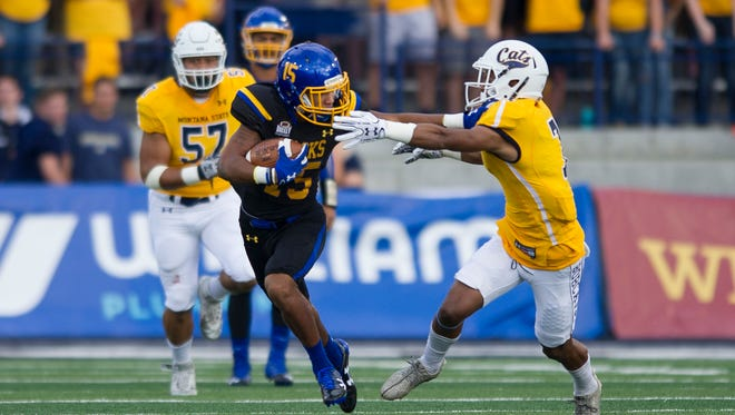 South Dakota State wide receiver Cade Johnson (15) fights off a Montana State defender during the first half of an NCAA college football game Saturday, Sept. 9, 2017, in Bozeman, Mont.