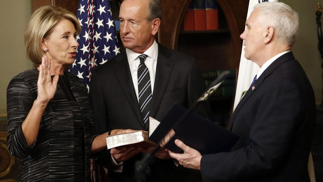 Vice President Mike Pence (right) swears in Education Secretary Betsy DeVos in the Eisenhower Executive Office Building in the White House complex on Tuesday as DeVos' husband Dick DeVos watches.