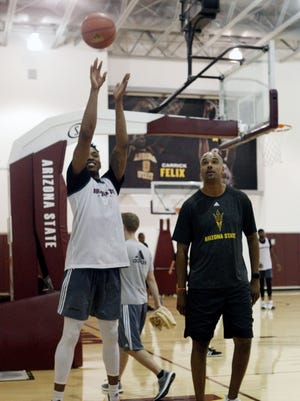 Freshman Kimani Lawrence practices free throws while assistant coach Anthony Coleman watches during a July 2017 workout.