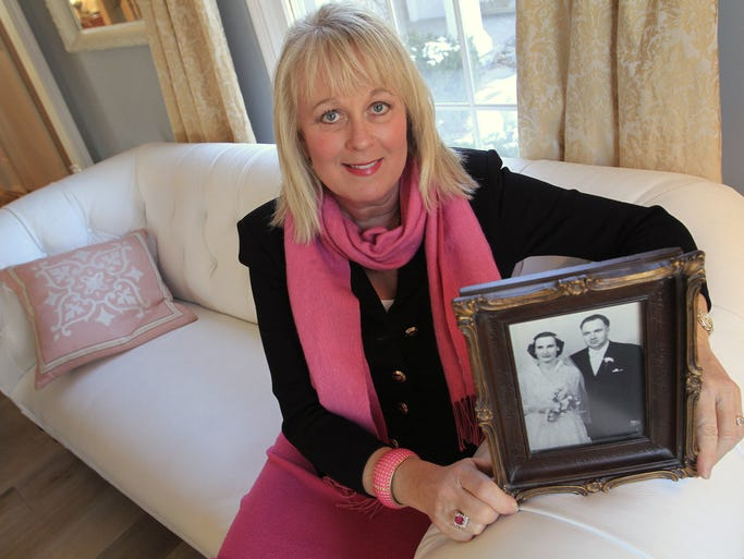 "Nela Wainscott poses with a wedding-day photo of her parents, Zenovia and Mykola Martyniuk, Thursday, March 6, 2014.  Her family is Ukrainian and is closely watching the news events developing in the Ukraine.  ""It is an abomination,"" she says passionately about Russia's activities.  ""Putin is following the Hitler rulebook,"" she adds.  Yet she glows as she talks about her heritage.  Her father was a freedom fighter, who worked to free the Ukraine from foreign occupation."