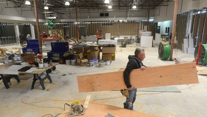 Mitch McKenney of Nyman National Inc, carries a board in the Planet Fitness under construction in the Colony Square Mall. The gym plans on opening in June.
