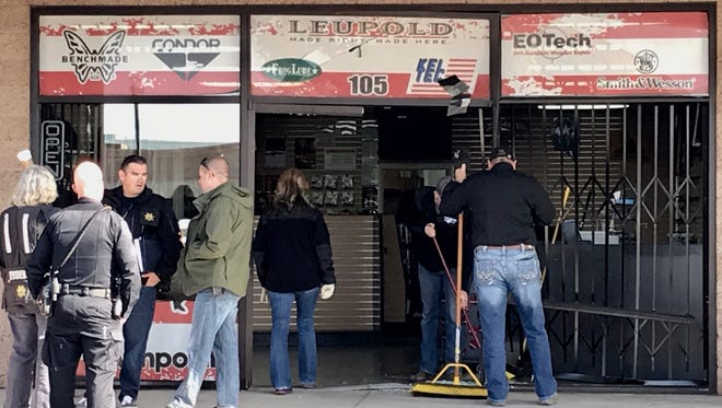 Officers with the Sparks Police Department investigate the scene where a car rammed into Sparks Black Rifle on Friday, April 13, 2018. A crew is also seen sweeping broken glass from the entrance of the shop.