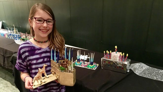Ava Goldner, 11, poses with her entry that won the children's menorah-making contest Dec. 16 at Congregation Micah in Brentwood.