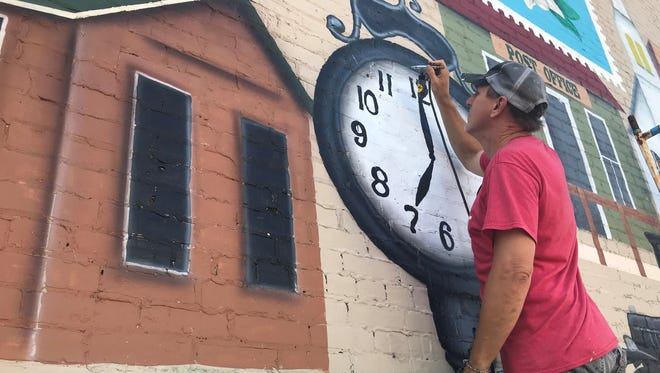 Matt Thone paints a mural on a wall located at Depot Street and Pigeon Roost Road in Olive Branch.