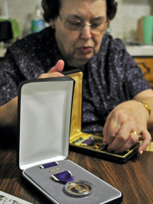 Shelva Moats, of Mont Alto, looks at medals she recived for her brother, Robert E. Meyers' military service.  Meyers was listed as Missing in Action during the Korean War, but his remains were discovered in a prisoner of war camp.