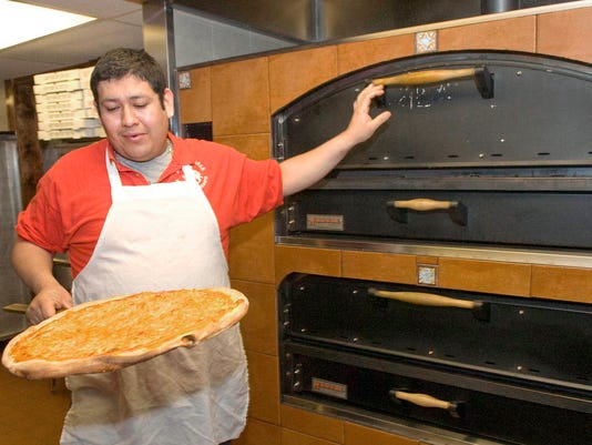 Eduardo Jurado takes a pizza out of the oven.