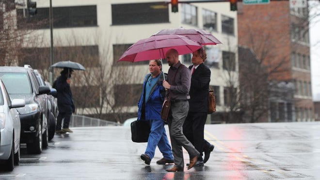 Rain falls on downtown commuters Monday morning.