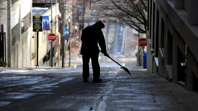 A man scrapes ice off of the sidewalk on Market Street in downtown Asheville during the lunch hour Tuesday.