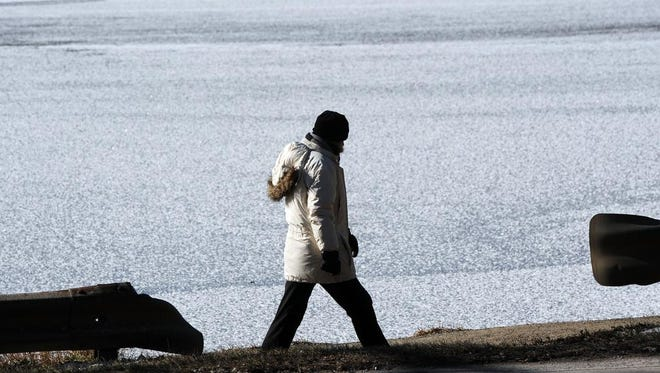 A woman strolls along a frost-covered Beaver Lake Friday morning. The lake began to freeze following days of record low temperatures.