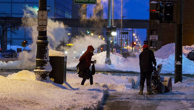A worker using a snowblower to clear the sidewalk along Fort Street in front of the federal courthouse in downtown Detroit on Feb. 2, 2015.  Steve Pepple/Detroit Free PRess