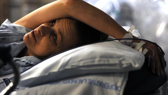 Debra Thomas waits for care in the Mission Hospital  Emergency Department where the 53-year-old reflects on her pain, and the fact she can not afford to pay for health care. She is uninsured, and prays each night she can be cured of an unknown brain illness.