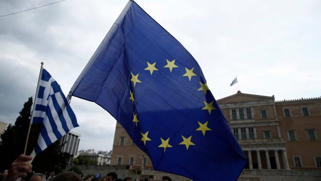 A demonstrator holds European Union and Greek flags during a rally on June 30, 2015, in Athens.