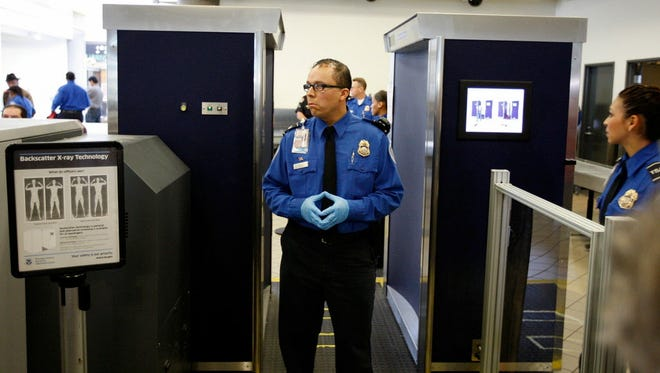 Transportation Security Administration officers stand near an Advanced Imaging Technology (AIT) full-body scanner at Los Angeles International Airport (LAX) on Nov. 22, 2010.