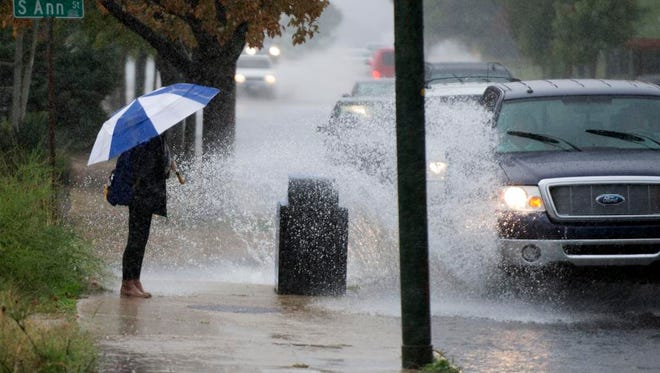 A wall of water kicked up from a truck drenches a woman walking on Patton Avenue during heavy rain Tuesday afternoon. The rain caused flooding in many areas around the area.