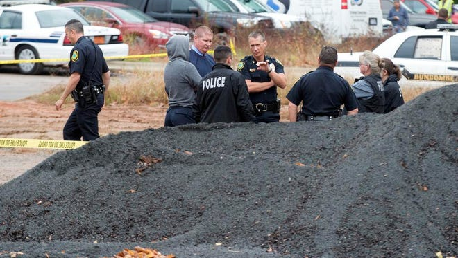 Officers investigate and search for clues in the case of two missing Buncombe women at the French Broad River Thursday.