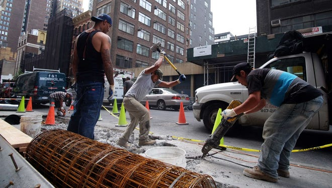 Workers break a concrete footpath July 2, 2015, beside a busy street in New York.