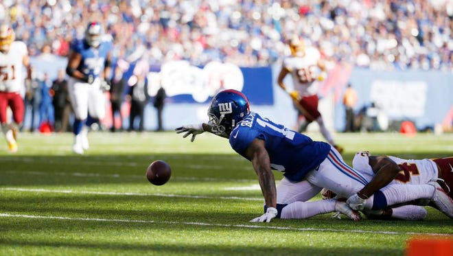 New York Giants wide receiver Odell Beckham loses control of the ball as Washington Redskins' Josh Norman tackles him during the second half of Sunday's game at MetLife Stadium in East Rutherford.