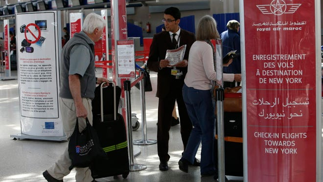 Airport staff inform passengers March 29, 2017, about a prohibition about electronics larger than cellphones on flights to the U.S., at the check in area at Casablanca Mohammed V International Airport, Morocco.
