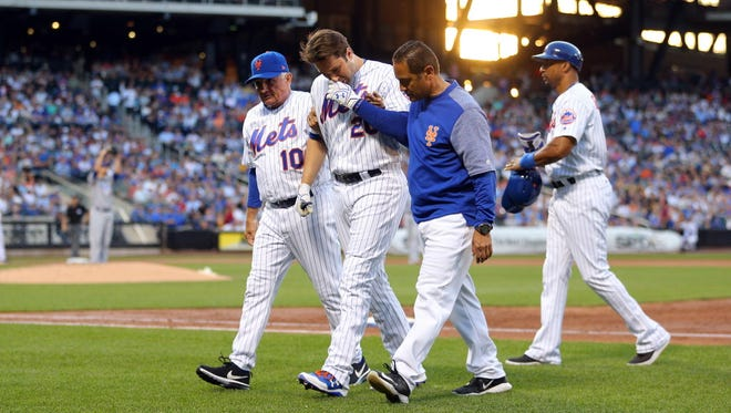New York Mets second baseman Neil Walker (20) is helped off the field by New York Mets manager Terry Collins (10) and trainer Ray Ramirez after sustaining a leg injury while running out a ground ball against the Chicago Cubs during the third inning at Citi Field.
