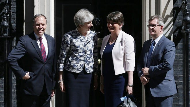 Britain's Prime Minister Theresa May, second from left, poses for a picture with Democratic Unionist Party (DUP) leader Arlene Foster, second from right, in central London on June 26.