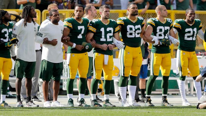Packers players link arms during the national anthem before their game on Sunday, September 24, 2017 at Lambeau Field in Green Bay, Wis.