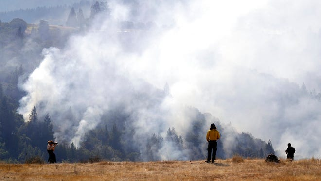 A firefighter, center, and two onlookers watch a smoldering wildfire from a hilltop, Sunday in Oakville. With the winds dying down, fire officials in California say they are finally getting the upper hand against the wildfires that have devastated wine country and other parts of the state over the past week. (AP Photo/Marcio Jose Sanchez)
