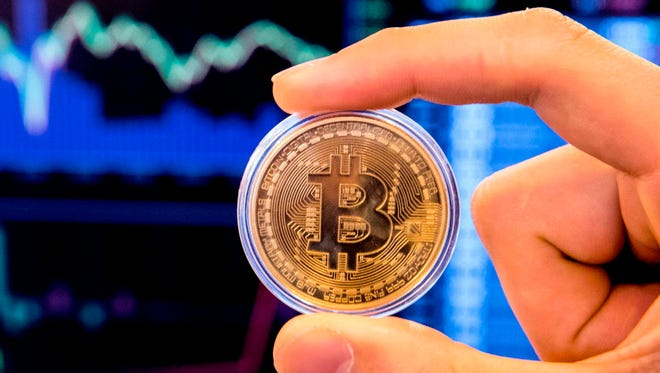 An Israeli holds a visual representation of the digital cryptocurrency Bitcoin.