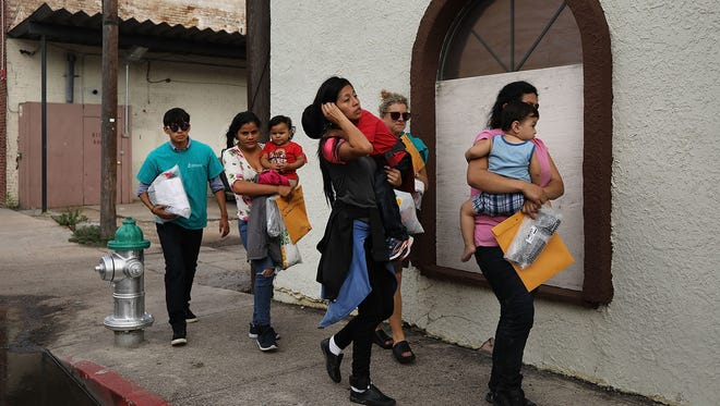 Migrants released from border detention in McAllen, Texas, walk to a relief center on June 22, 2018.