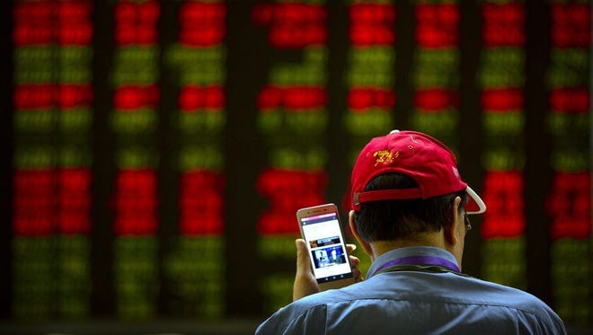 A Chinese investor listens to a news report on his smartphone as he monitors stock prices at a brokerage house in Beijing, on July 6, 2018.