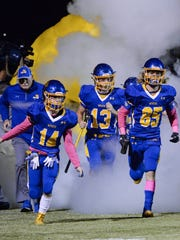 Wren High School players run on the field before kickoff