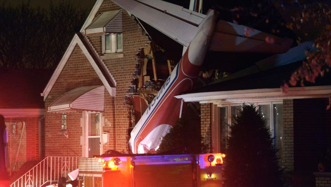 A small twin-engine cargo plane is seen after it crashed into a home on Chicago's southwest side early Tuesday morning, Nov. 18, 2014, shortly after taking off from Midway International Airport.