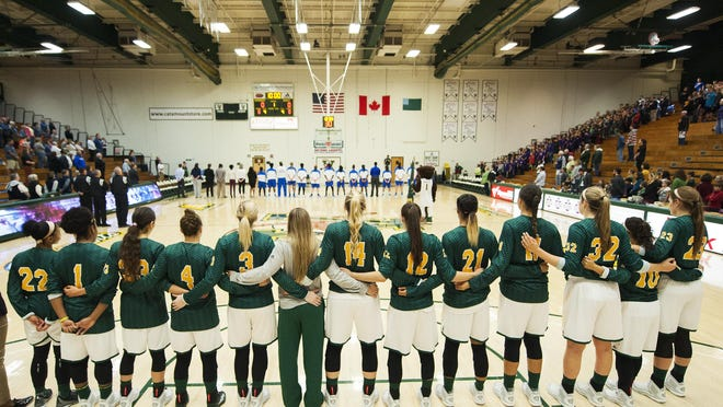 Both teams line up to listen to the national anthem during the women's basketball game between the Central Connecticut Blue Devils and the Vermont Catamounts at Patrick Gym on Friday morning.