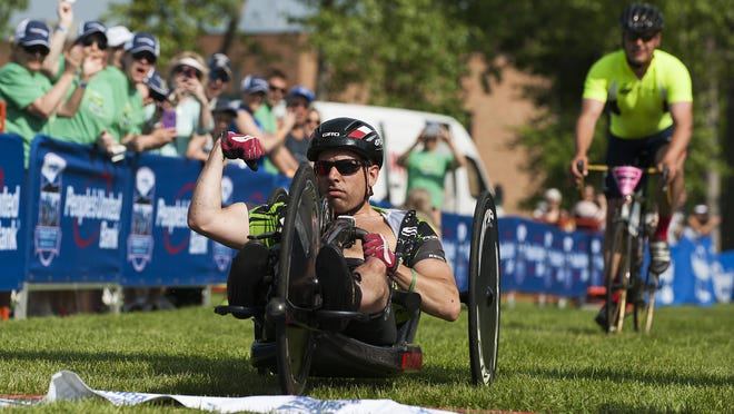 Jeremy Shortsleeve of Jericho crosses the finish line in first place in the handcycle part of thet People's United Bank Vermont City Marathon on Sunday morning.