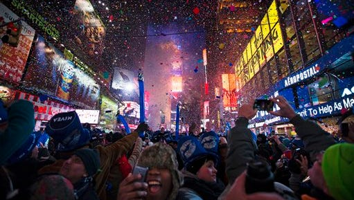 This Jan. 1, 2014, file photo shows revelers cheering under falling confetti at the stroke of midnight during the New Year's celebrations in Times Square, in New York. Americans are closing out 2014 on an optimistic note, according to a new Associated Press-Times Square Alliance poll. Nearly half predict that 2015 will be a better year for them than 2014 was, while only 1 in 10 think it will be worse.