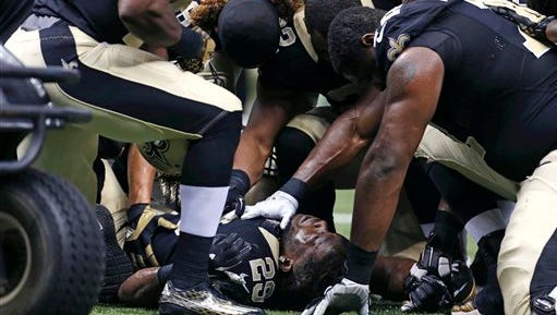 New Orleans Saints running back Khiry Robinson (29) is comforted by teammates on the field after being injured in the first half of an NFL football game against the New York Giants in New Orleans, Sunday.