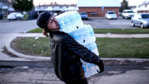 Flint resident Christopher Kabel carries multiple cases of bottled water to help hand out to residents at River Park Apartments in Flint on Monday April 4, 2016.