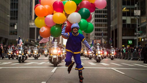 A performer carries balloons across Sixth Avenue during the Macy's Thanksgiving Day Parade, in New York, Thursday, Nov. 24, 2016.