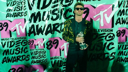 "FILE - In this Wednesday, Sept. 6, 1989 file photo, musician George Michael holds his trophy after winning the 1989 Video ""Vanguard Award"" for his ""Father Figure"" video during the MTV Music Awards at the Universal Ampitheatre in Universal City, Calf. Michael, who rocketed to stardom with WHAM! and went on to enjoy a long and celebrated solo career lined with controversies, has died, his publicist said Sunday, Dec. 25, 2016. He was 53."