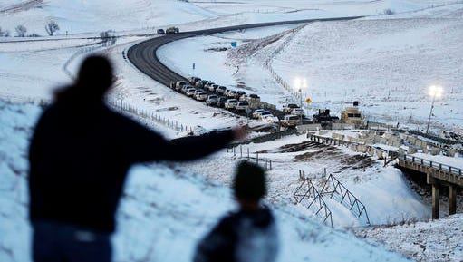 FILE- In this Dec. 3, 2016, file photo, law enforcement vehicles line a road leading to a blocked bridge next to the Oceti Sakowin camp where people have gathered to protest the Dakota Access oil pipeline in Cannon Ball, N.D. North Dakota Sen. John Hoeven said Tuesday, Jan. 31, 2017, that the Acting Secretary of the Army has directed the Army Corps of Engineers to proceed with an easement necessary to complete the Dakota Access pipeline.