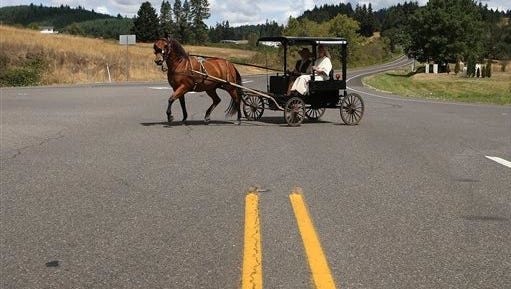 In this photo on Wednesday, Oct. 8, 2014, Eli and Cheryl Cutler drive their homemade buggy pulled by a horse named Whiskey across the highway near Lorane, Ore. The couple have chosen to live a simple life as they caretake property in rural Lane County south of Eugene.