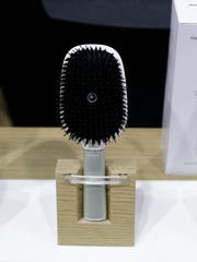 Hair Coach smart hairbrushes are displayed at the Withings