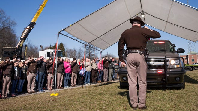 Mike Nielsen, Boone County Sheriff, salutes the vehicle of Deputy Jacob Pickett, outside the Boone County Sheriff's Office and Jail, home office of  Pickett, Lebanon, Saturday, March 3, 2018. The deputy was fatally shot a day earlier while helping local police serve a warrant.
