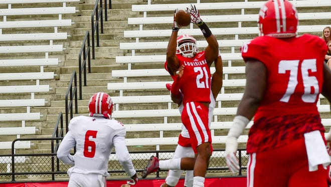 UL wide receiver Keenan Barnes (21) goes up high to make a grab for the Red squad in Saturday's spring game at Cajun Field.