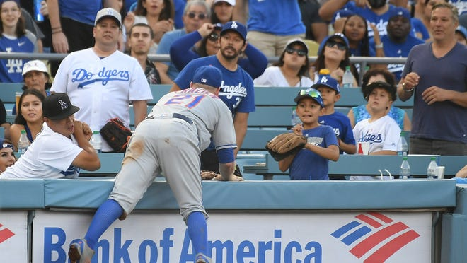 Sep 3, 2018; Los Angeles, CA, USA; New York Mets third baseman Todd Frazier (21) goes over the wall to catch a ball hit by Los Angeles Dodgers center fielder Alex Verdugo (61) in the second inning  at Dodger Stadium. Mandatory Credit: Richard Mackson-USA TODAY Sports ORG XMIT: USATSI-376719 ORIG FILE ID:  20180903_lbm_am8_007.JPG